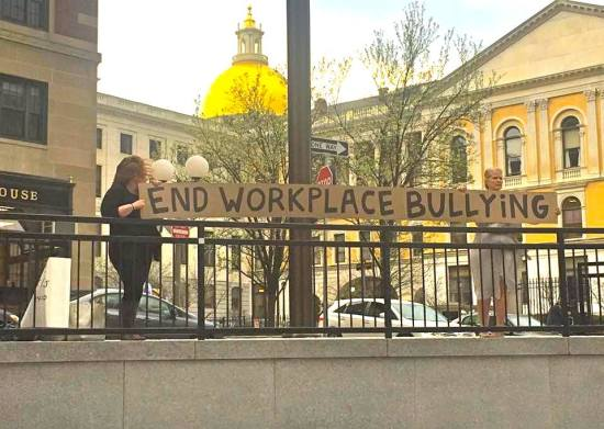 Deb Falzoi and Torii Bottomley holding sign near the MA State House